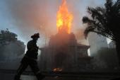 Пожарные работают над тушением пожара в приходе Ла-Асунсьон в окрестности Plaza Italia после протеста в Сантьяго [Elvis Gonzalez/EPA]