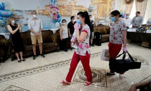 Медсестра несет новорожденного, чтобы встретить его родителей, пока иностранные пары ждут, чтобы забрать своих младенцев в отеле Venice, принадлежащем клинике BioTexCom в Киеве
