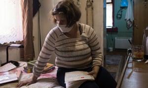 Татьяна Шульжинская просматривает свои медицинские карты в своем доме в Чернигове на севере Украины
