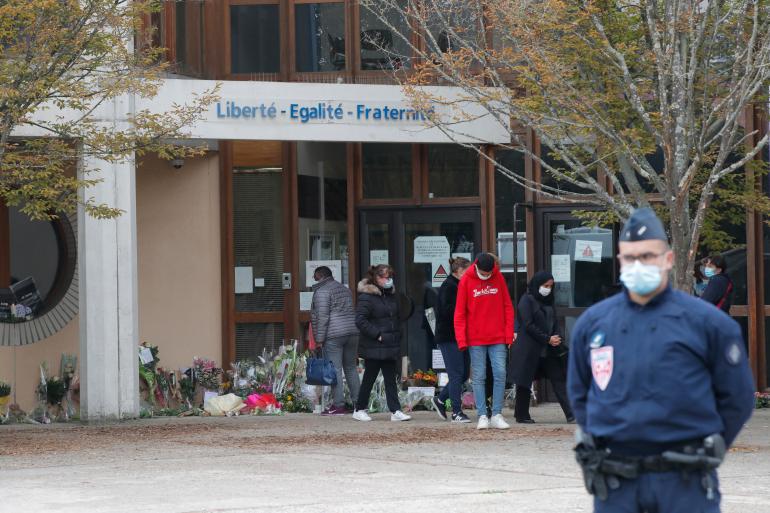 Офицер ОМОН стоит на страже когда школьники уезжают после того, как отдавали дань уважения убитому учителю истории, суббота, 17 октября 2020 г., в Конфлан-Сент-Онорин, к северо-западу от Парижа [MichelEuler/AP)