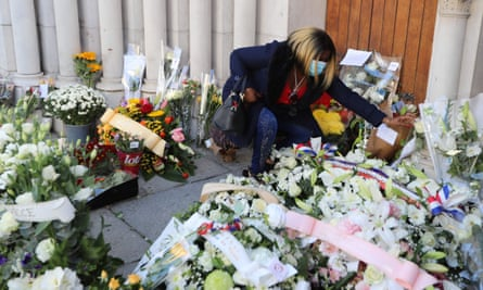 Женщина возлагает цветы перед базиликой Нотр-Дам-де-л'Ассупшен в Ницце.