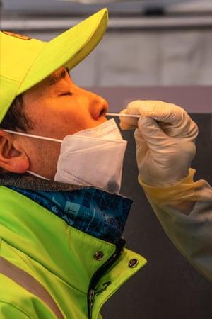 Мужчина в защитной маске делает мазок из носа на временном участке тестирования на Covid-19 на площади Сеула.