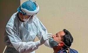 Медицинский работник берет образец мазка для анализа на Covid-19 у мужчины в Боготе 13 января 2021 года.