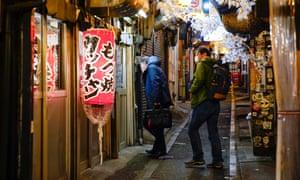 Посетители ищут место для напитков на крошечной пивной улице Синдзюку. в Токио, Япония, 13 января 2021 года.