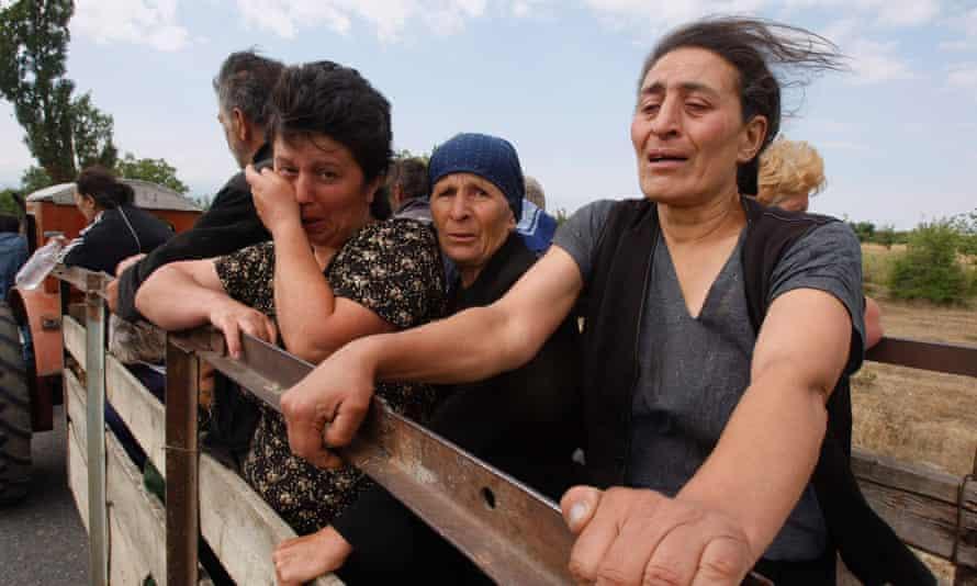 Грузинские женщины плачут, покидая свою деревню недалеко от города Цхинвали, Грузия, 10 августа 2008 года.