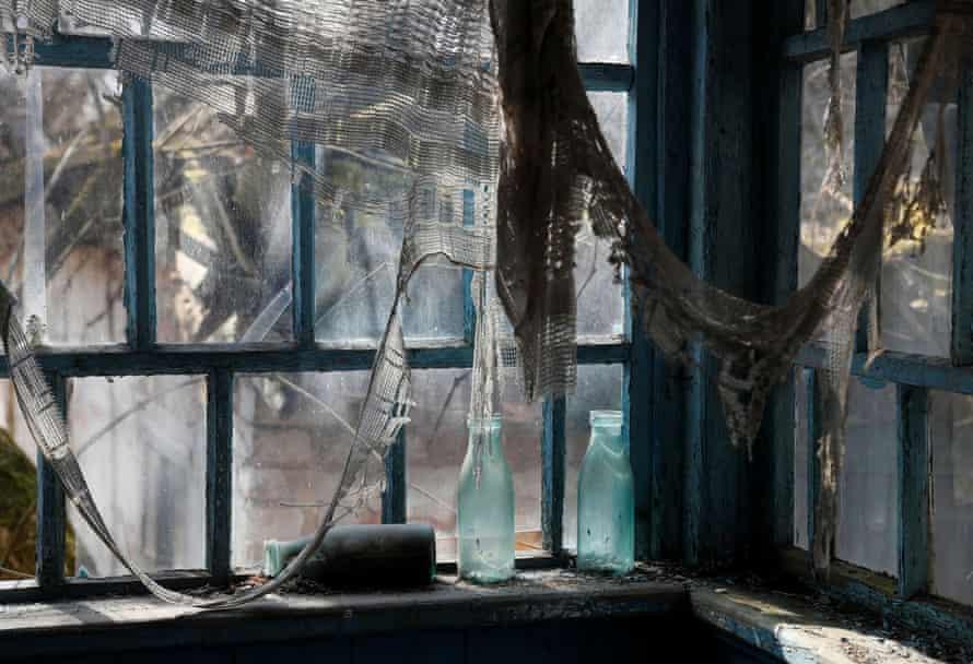 Новое безопасное ограждение над старым саркофагом, прикрывающее поврежденный четвертый реактор, с заброшенным городом Припять на переднем плане. [19659009] Дом в заброшенном селе Залесье