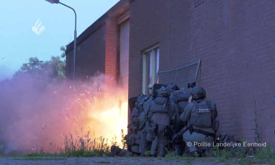 Фотография полицейских, собирающихся в группу у стены здания, когда у двери раздается сильный взрыв