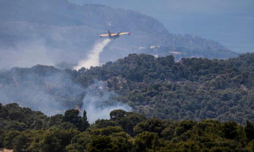 Пожарный самолет распыляет воду, чтобы тушить лесной пожар.